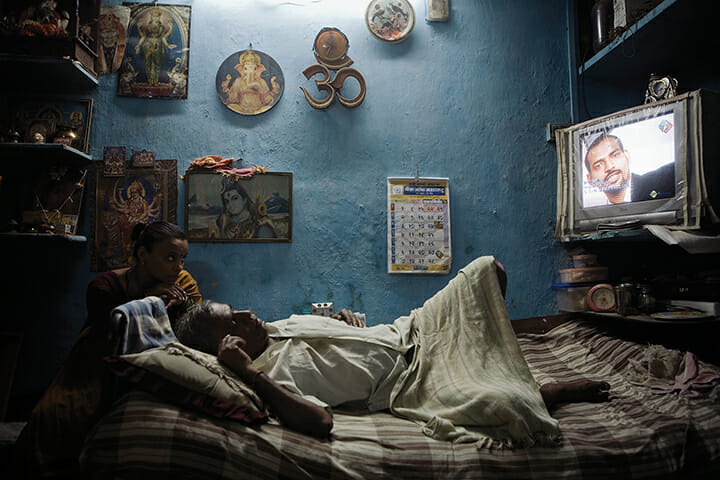 An Indian man and his daughter-in-law watch television at their home in Dharavi in 2008. Residents of Dharavi fear they will be moved from their existing homes to the outskirts of Mumbai when slum redevelopment plans go ahead.