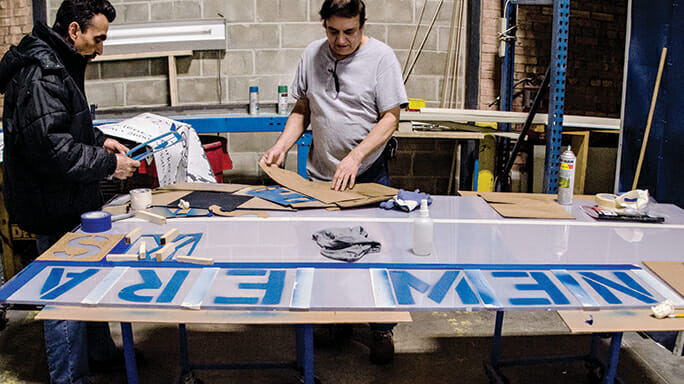 Rodolfo Zoto and Norberto Román make signage for the New Era Windows plant.