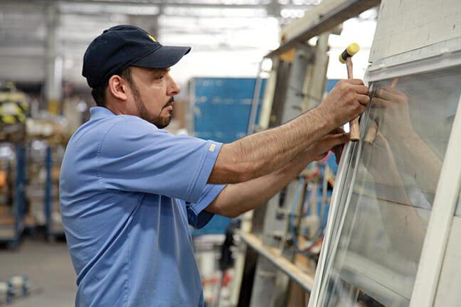 Gilberto Reyes prepares a window sash for installation.
