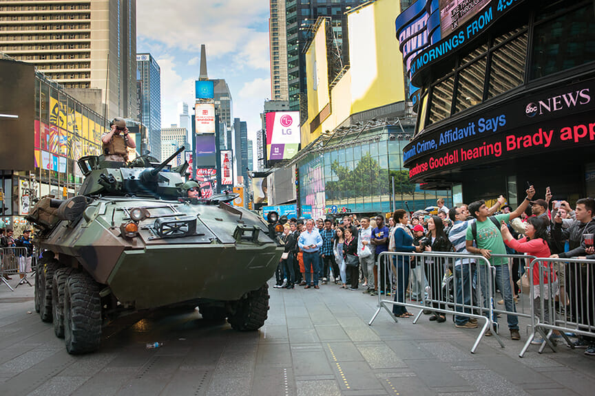 US Marines drive through Times Square in an armored personnel carrier, which looks like a tank, with demonstration weapons including rifles.