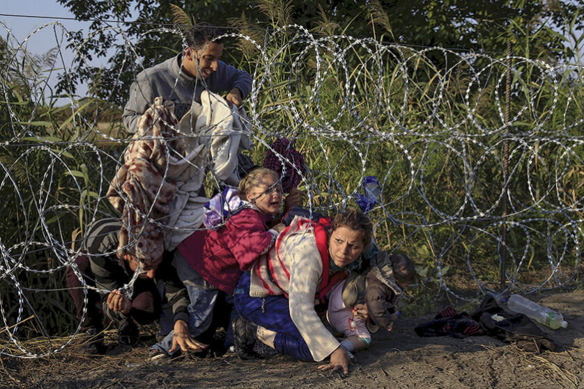 Syrian migrants cross under a fence as they enter Hungary at the border with Serbia, near Roszke, August 27, 2015. Reuters and The New York Times shared the Pulitzer Prize for breaking news photography for images of the migrant crisis in Europe and the Middle East. REUTERS/Bernadett Szabo