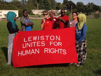 "a group of volunteers hold a banner reading ""Lewiston Unites for Human Rights"""