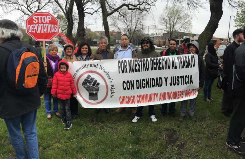 "Protestors hold signs that read ""Stop Deportations"" and ""Por Nuestro Derecho al Trabajo Con Dignidad y Justicia, Chicago Community and Workers' Rights."