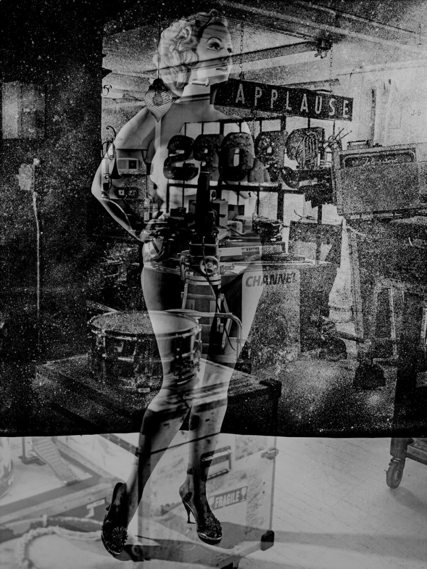 A black-and-white collage in which a voluptuous woman with a 1950s hairstyle is superimposed over various photos of musical instruments and neon signage.
