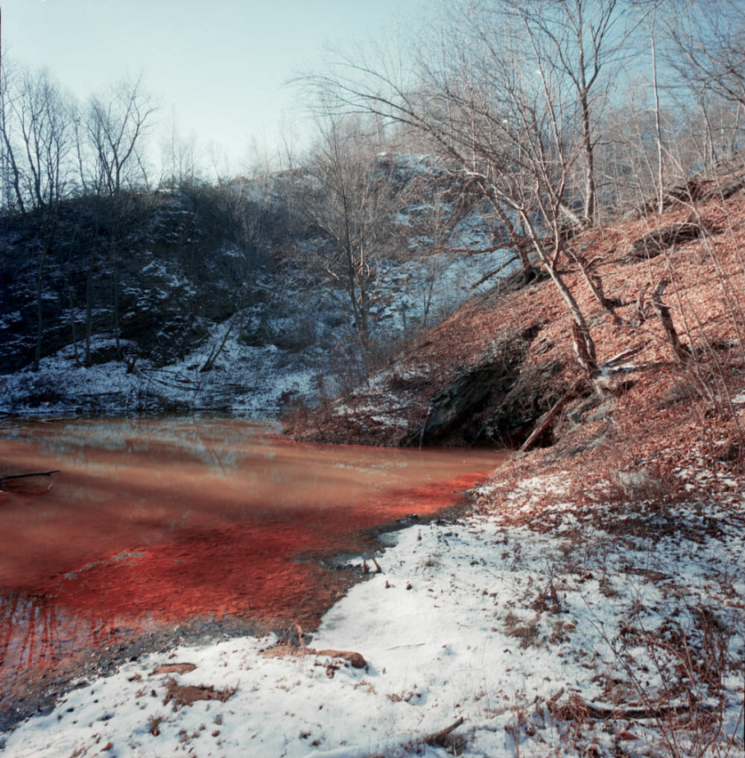 A photograph by Jeremy Blakeslee showing a reddish brown creek filled with coal mine tailings in the snowy woods of Centralia, PA.
