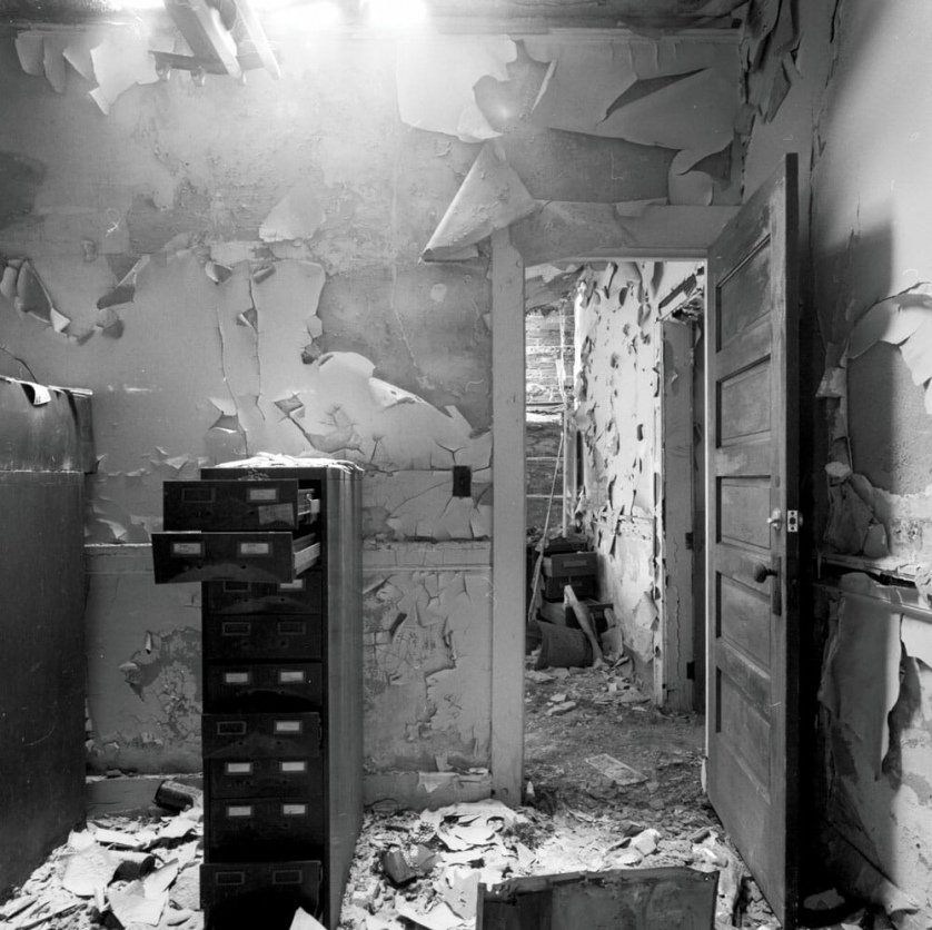 A photograph by Jeremy Blakeslee showing an abandoned police station in High Park, Detroit. A file cabinet stands open, papers litter the floor, paint peels from the walls.