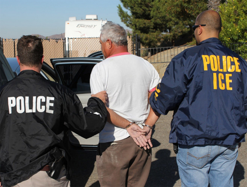 "ICE agents take someone into custody during ""Operation Cross Check."""