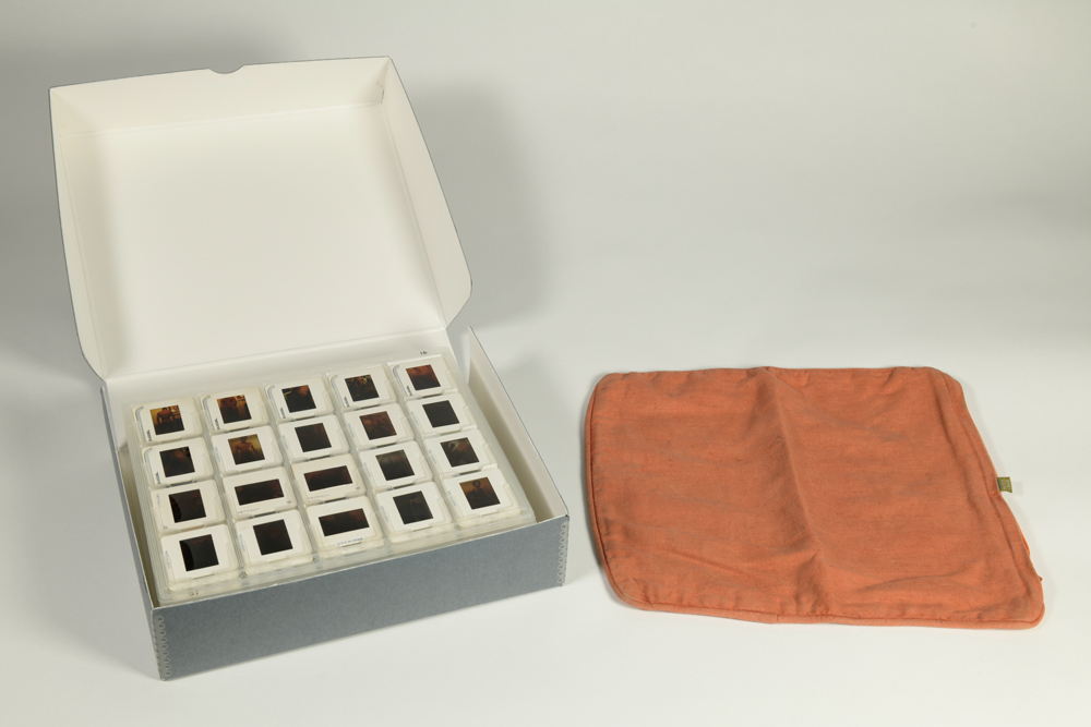An orange cushion cover is placed next to a box of slides.