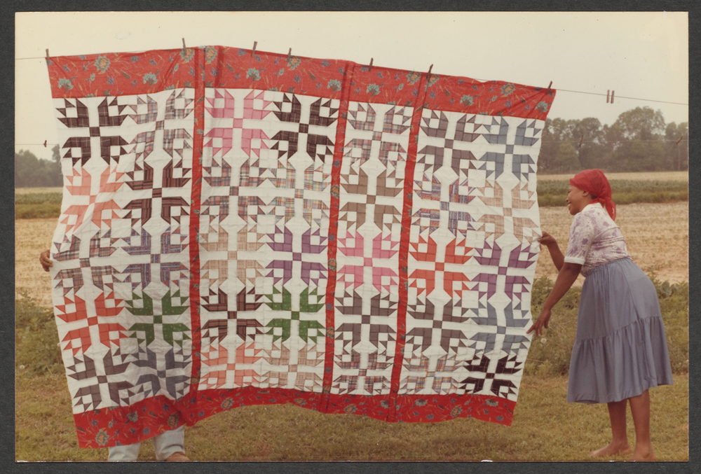 A woman hanging a quilt from a clothesline.