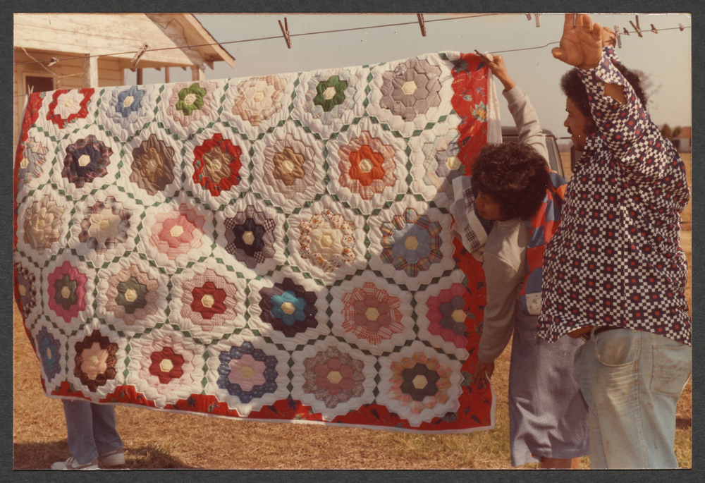 Men hanging a quilt from a clothesline.
