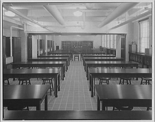 Desks and chairs in an empty 1920s college classroom.
